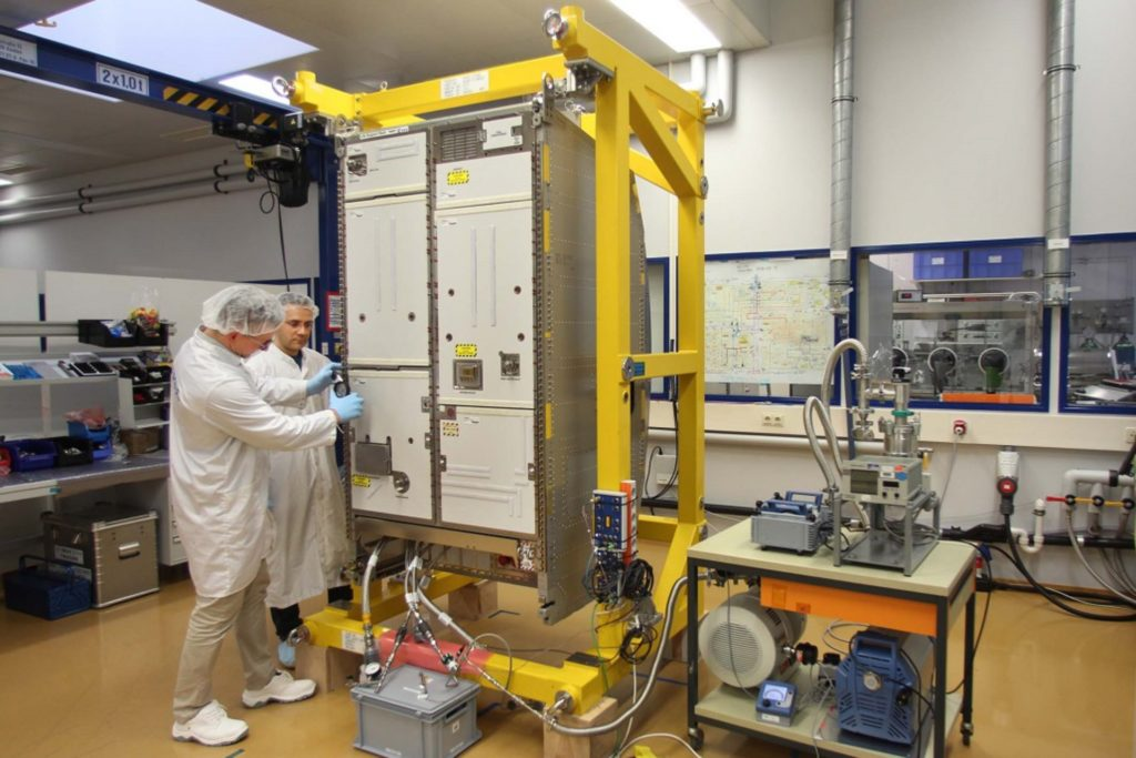 Two technicians point to large instrument box.